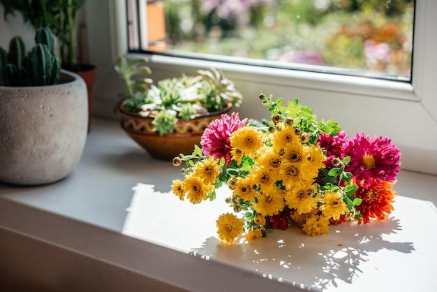 Bellissimo bouquet autunnale di aster giallo e fiori di crisantemo sul davanzale della finestra