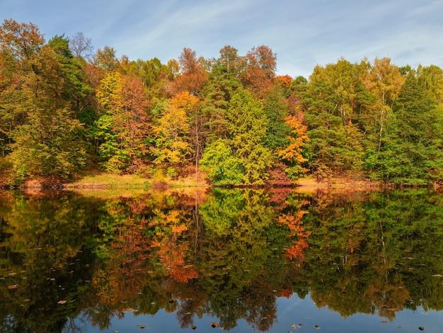 Bellissimo paesaggio autunnale con alberi rossi in riva al lago.