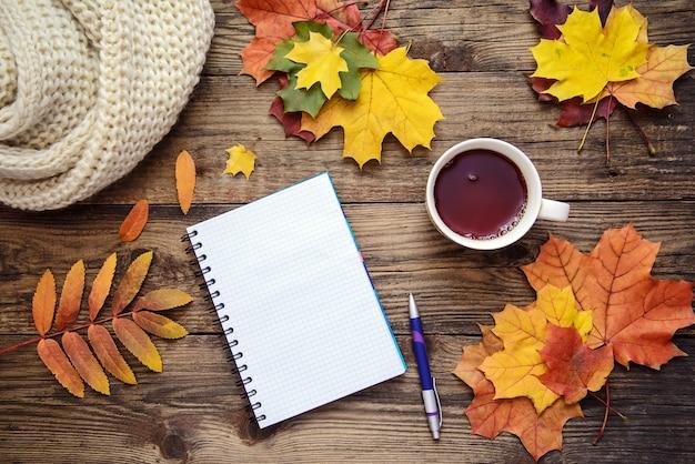 Bella foto autunnale con foglie gialle, rosse e arancioni, una tazza di tè, una sciarpa e un pezzo di carta con penna su superficie di legno