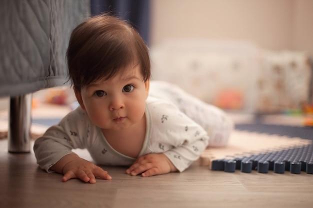 Bellissimo neonato con i capelli scuri in pigiama luminoso che impara a gattonare e sdraiarsi a pancia in giù sul pavimento nella scuola materna