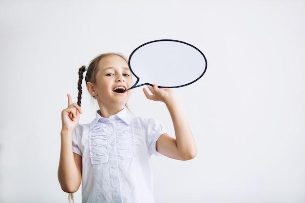 Bella bambina in una classe a scuola su uno sfondo bianco con la nuvola di pensieri dal ritratto comico felice con il concetto