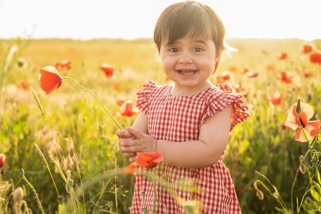Bella neonata in vestito rosso sul campo dei papaveri al tramonto di estate.