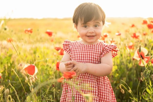 Bella bambina in abito rosso sul campo di papaveri al tramonto estivo