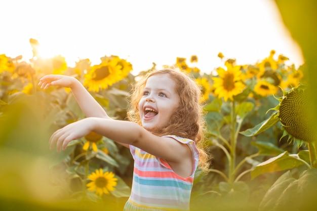 Bella bambina in piedi tra i girasoli e alzando le mani