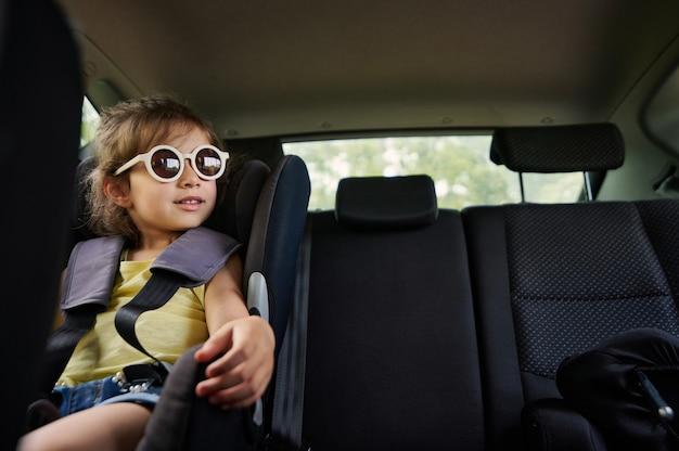 Una bellissima bambina con gli occhiali da sole si siede in un seggiolino per auto in macchina e guarda fuori dalla finestra. viaggiare sicuri con i bambini in macchina