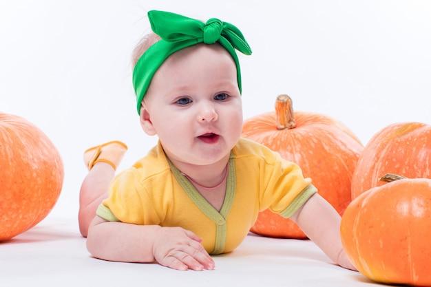 Bellissima bambina in un corpo giallo con fiocco verde in testa