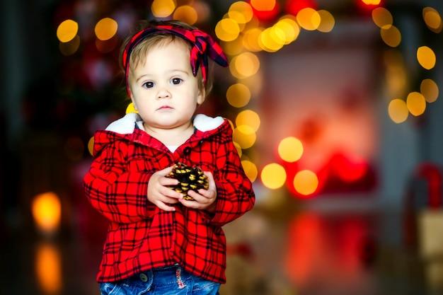 Bel bambino alla vigilia di capodanno in mezzo a luci festive luminose incandescenti.