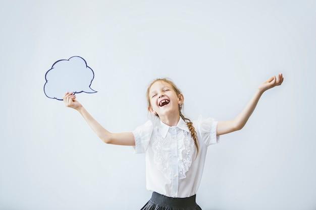 Bella bambina della scuola in classe a scuola su uno sfondo bianco ritratto felice con un concetto