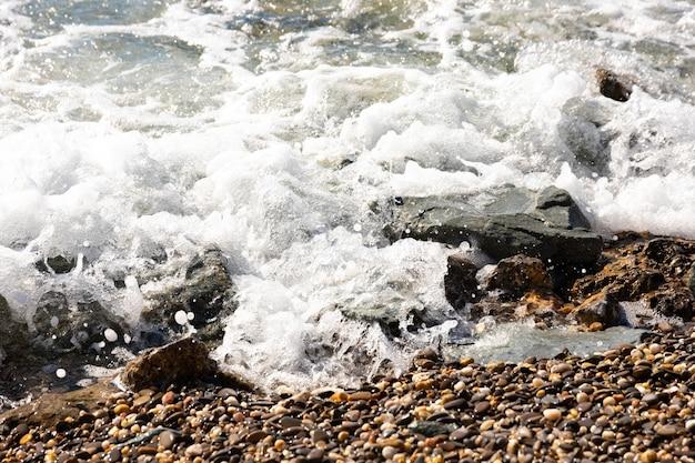 Bella immagine di sfondo di ciottoli sulla spiaggia con onde e mare.