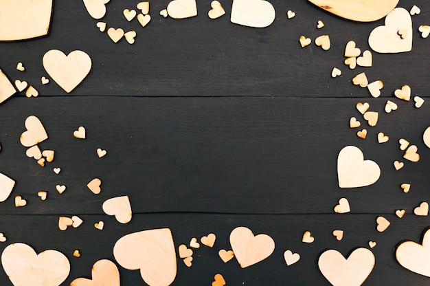 Un bellissimo sfondo con un sacco di cuori in legno sul tavolo scuro