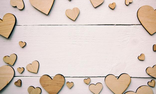 Un bellissimo sfondo con un sacco di cuori in legno sul tavolo bianco