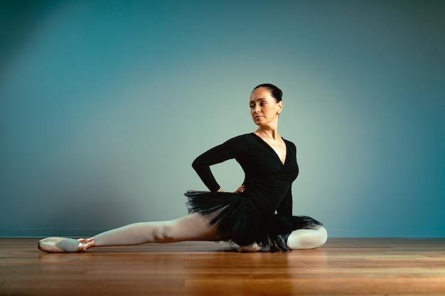 Bella ballerina in scarpe da punta che si siede sul pavimento