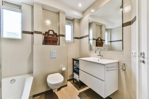 Bellissimo bagno con un grande specchio e pareti bianche