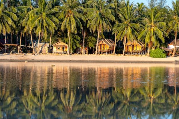 Bellissima baia con palme da cocco e bungalow in legno che si riflette nell'acqua di mare