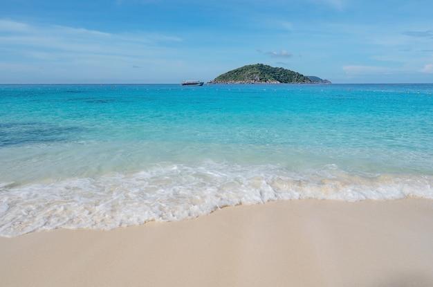 Bellissima spiaggia e mare tropicale con onde che si infrangono sulla spiaggia sabbiosa arcipelago di piccole isole al parco nazionale di similan concetto di viaggio e tour in thailandia.