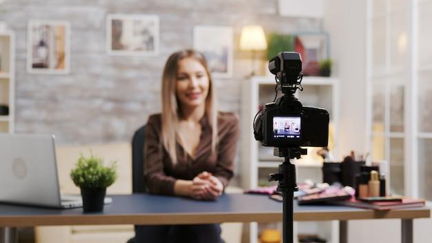 Bella influencer di bellezza che registra un tutorial su come usare il trucco. donna attraente che filma un vlog.