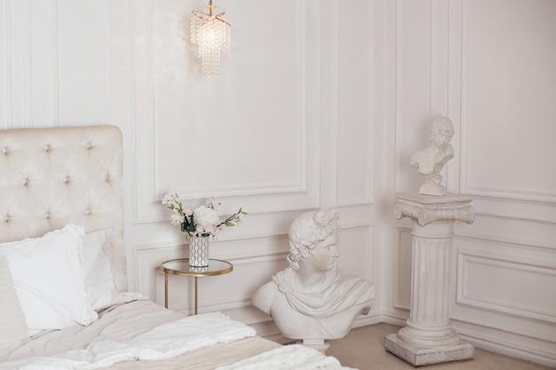 Bella camera da letto nei colori beige con sculture antiche
