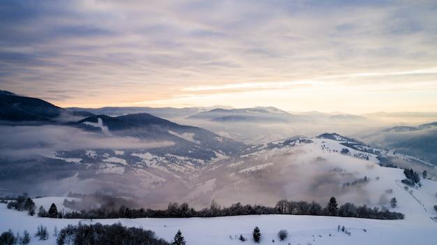 Bella vista ammaliante di montagne e rocce con foreste di abete rosso in una gelida sera d'inverno con nebbia e sole al tramonto
