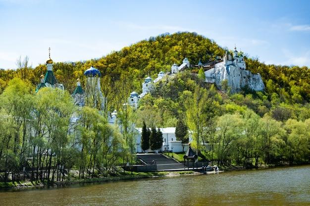 Bella vista ammaliante della chiesa ortodossa e del monastero situato sulle rive del fiume sulle colline ricoperte di verdi boschetti in una soleggiata giornata autunnale. concetto di vita spirituale