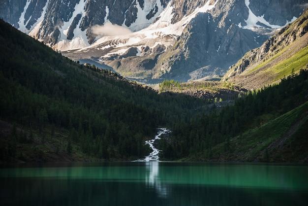 Bellissimo grande ghiacciaio alla luce del sole, montagne rocciose innevate, nuvole basse, foresta di conifere sulle colline, lago di montagna e insenatura dell'altopiano riflessa in acque limpide. atmosferico scenario alpino al mattino soleggiato.