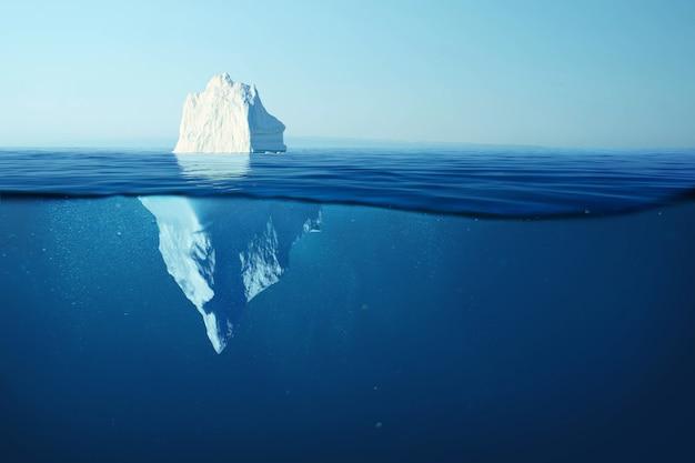 Bello grande iceberg bianco sott'acqua. il riscaldamento globale e lo scioglimento dei ghiacciai, concetto. iceberg nell'oceano con vista sott'acqua. acqua cristallina. pericolo nascosto e riscaldamento globale