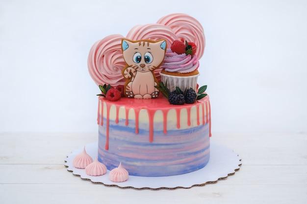 Bellissima torta di compleanno con un simpatico gattino decorato con meringa rosa, more fresche e lamponi