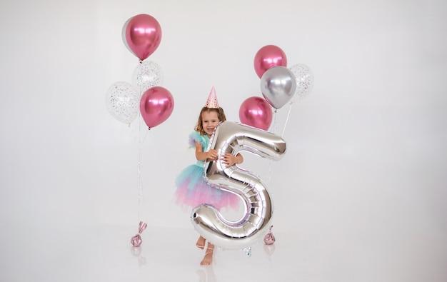 La bella ragazza di compleanno tiene un foglio numero cinque su uno sfondo bianco festivo con una copia dello spazio