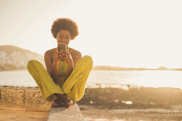 La bellissima modella africana di razza nera con bei capelli usa lo smartphone per sedersi vicino all'oceano