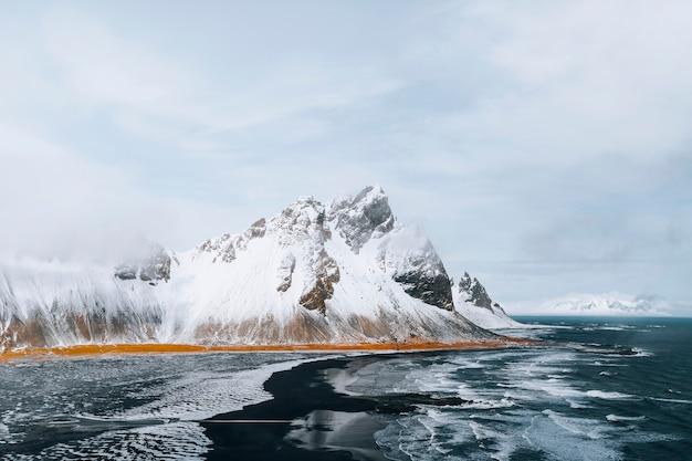 Bellissima spiaggia di sabbia nera in inverno a vestrahorn in islanda
