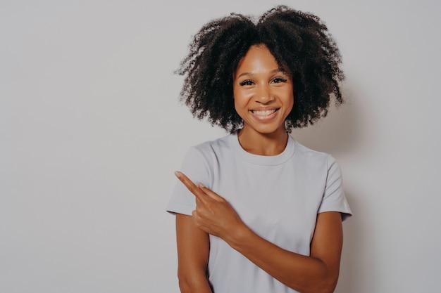 Bella donna nera che indossa abiti casual, allegra con un sorriso raggiante sul viso che punta con la mano e il dito verso l'alto con un'espressione facciale felice e naturale, copia spazio per la pubblicità