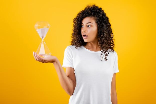 Bella donna di colore con la clessidra isolata sopra giallo