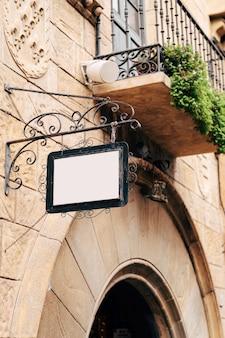 Bella insegna in bianco in una cornice di metallo forgiato è appesa a un muro di pietra di un edificio contro a