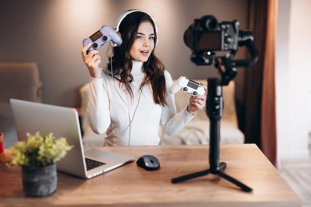 La bella donna blogger in cuffia è in diretta streaming parlando di videogiochi. influencer giovane donna si diverte in live streaming con laptop indoor.