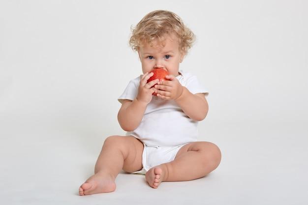 Il bello ragazzino dai capelli ricci biondo mangia la mela rossa fresca, prima colazione sana