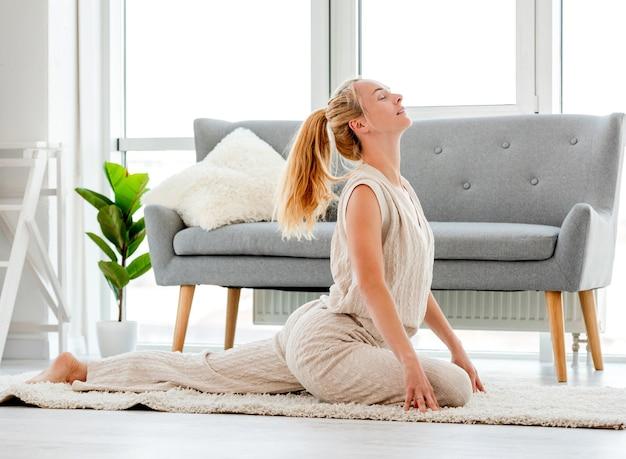 Bella ragazza bionda allungare il suo corpo durante l'allenamento yoga mattutino in camera con la luce solare