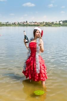 Bella bionda in posa in acqua con champagne