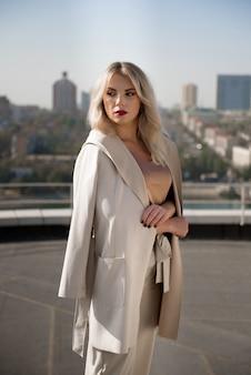 Bella donna bionda in cappotto beige in piedi sul tetto della casa.