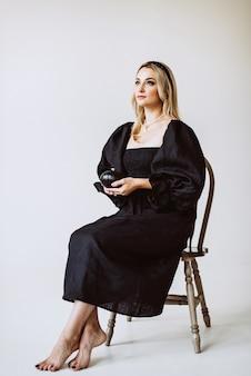 Bella donna bionda in abito di lino nero con una zucca in mano. moda etnica, tessuto naturale. messa a fuoco selettiva morbida.