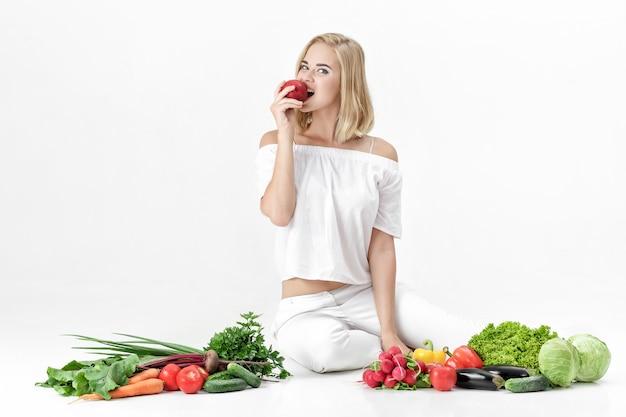 Bella donna bionda in abiti bianchi e un sacco di verdure fresche su uno sfondo bianco. la ragazza sta mangiando la nettarina