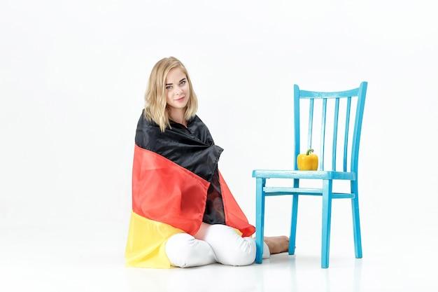 Bella donna bionda con la bandiera della germania e verdure. esportazione e importazione di ortaggi