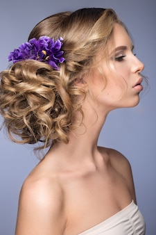 Bella donna bionda con fiori viola sulla sua testa