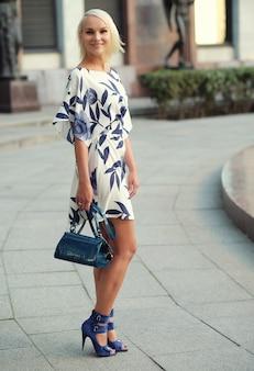 Bella giovane donna bionda che indossa un vestito e cammina per strada