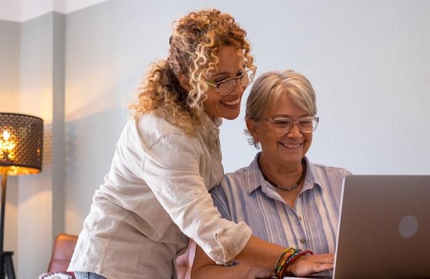 Bella figlia adulta bionda che insegna a sua madre come utilizzare la rete con un computer portatile digitale. concetto di condivisione e complicità.