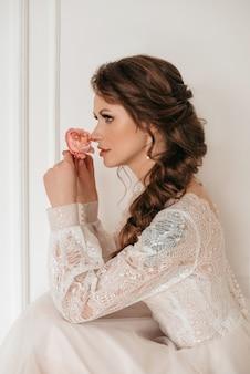 Bella sposa bionda con bouquet di fiori primaverili all'aperto.
