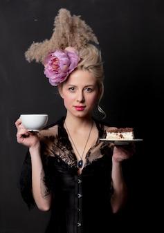 Bella contessa bionda con la torta e la tazza