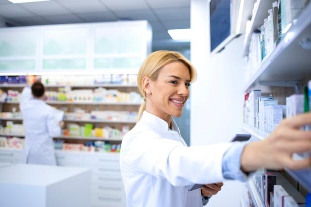 Bella bionda femmina operaio farmacia che organizza i farmaci sullo scaffale in drug store