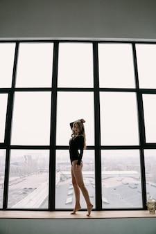 Bella ragazza bionda in una tuta nera vicino a una grande finestra