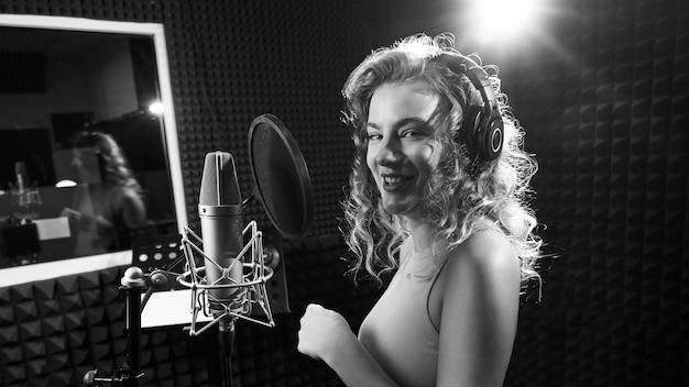 Bella ragazza bionda che canta emotivamente la canzone in studio di registrazione con microfono professionale e cuffie, crea un nuovo album di tracce, colpo di artista vocale in bianco e nero, faccia del primo piano