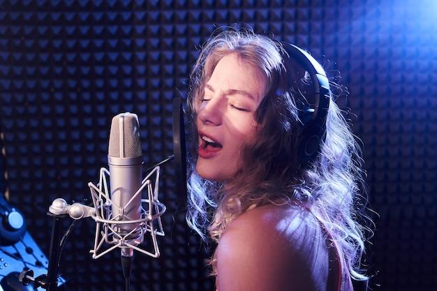 Bella ragazza bionda che canta emotivamente una canzone in studio di registrazione con microfono professionale e cuffie, crea un nuovo album di brani, artista vocale in luce al neon blu rosa, viso primo piano, karaoke
