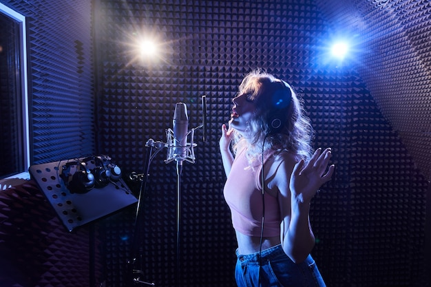Bella ragazza bionda che canta emotivamente la canzone in studio di registrazione con microfono professionale e cuffie, crea un nuovo album di brani, artista vocale in luce al neon blu rosa